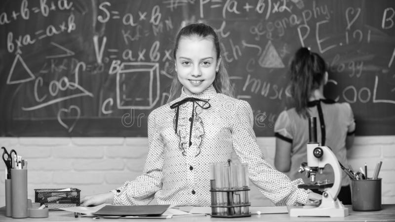 De meisjes bestuderen chemie in school De chemische reacties van microscoopreageerbuizen Leerlingen bij bord Fascinerende wetensc stock foto