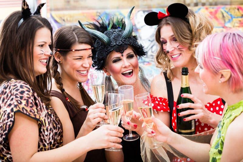 De meisjes in Carnaval paraderen clinking glazen met champagne stock afbeeldingen