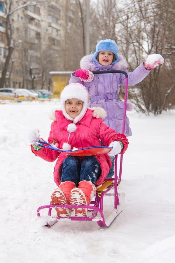 De meisjes in de binnenplaats van het berijden van een sneeuwslee verheugen zich stock foto's