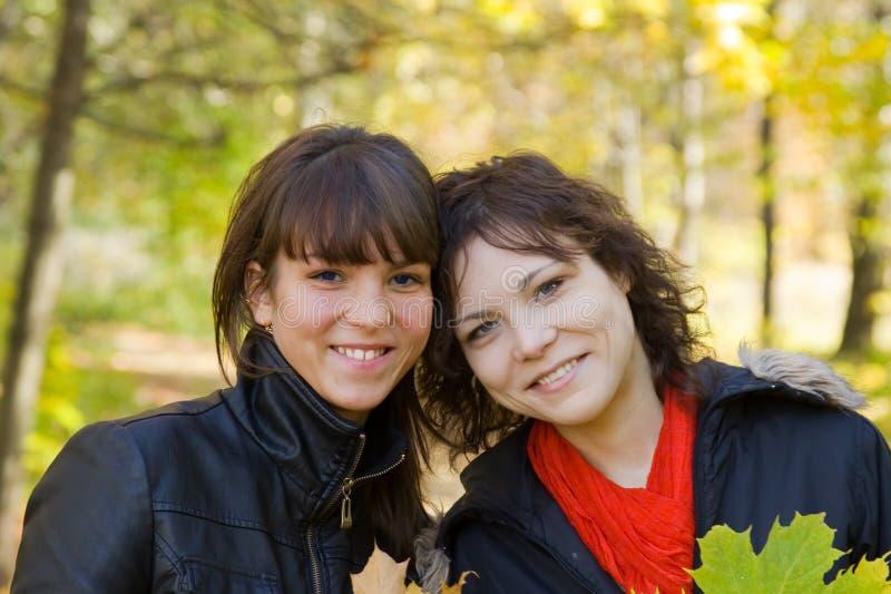 De meisjes in de herfst parkeren royalty-vrije stock afbeeldingen
