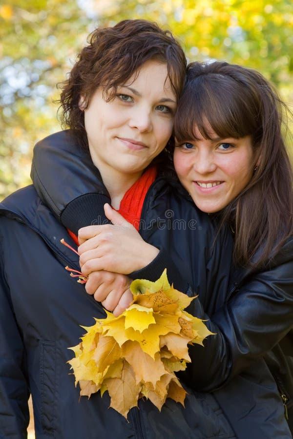 De meisjes in de herfst parkeren stock foto