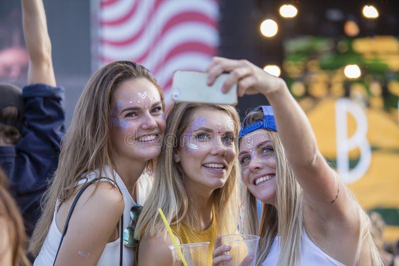 De meisjes is deelnemers van cultureel en muziekfestival Sziget in Boedapest, Hongarije Mooie meisjes die selfie op telefoon in S royalty-vrije stock afbeeldingen
