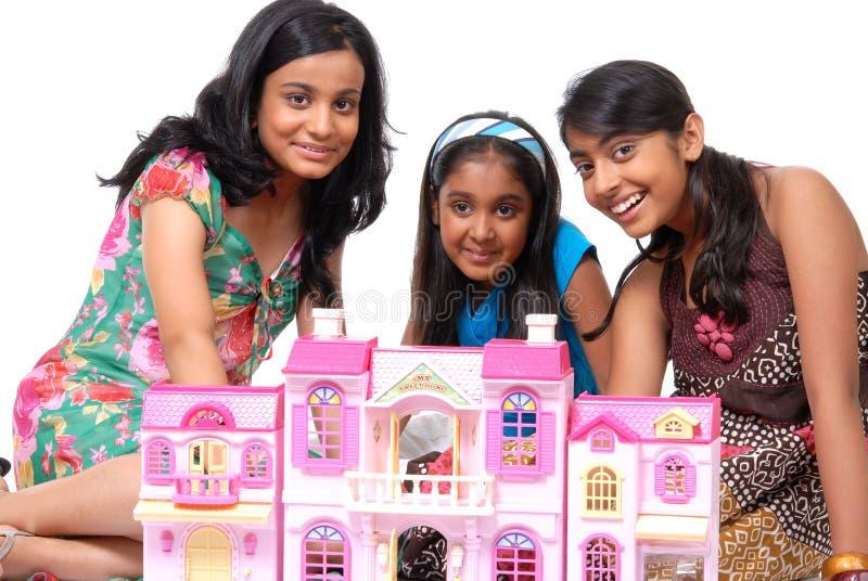 De meisjes die met pop spelen huisvesten stock foto