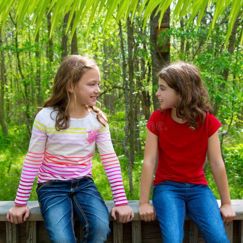 De meisjes die van de kinderenvriend op het bos van het wildernispark spreken royalty-vrije stock foto's