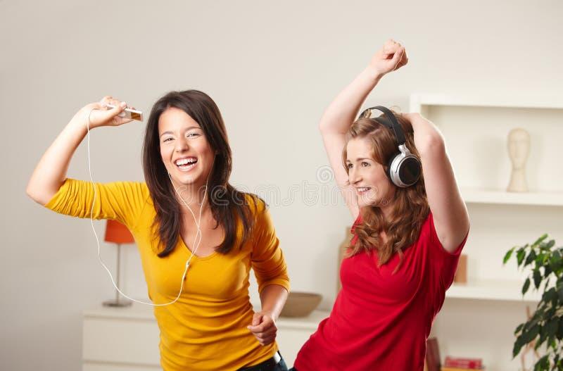 De meisjes die van de tiener aan muziek luisteren stock afbeeldingen