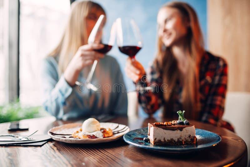 De meisjes drinkt rode wijn en eet dessert stock foto's