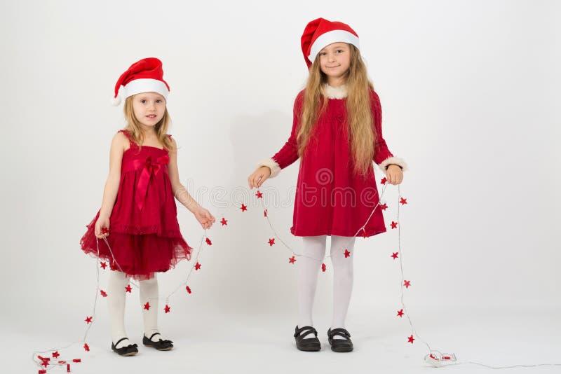 De meisjes in een rood kleden zich in kappen Santa Claus houdend een slinger stock foto's