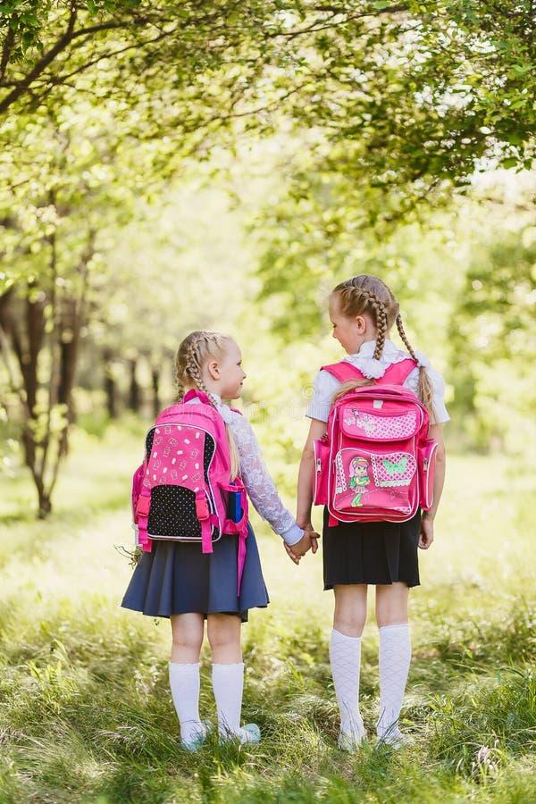 De meisjes in eenvormige school en met rugzakken gaan achteruit stock afbeeldingen