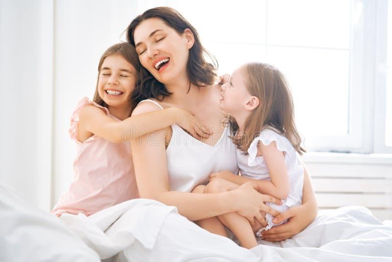 De meisjes en hun moeder genieten van zonnige ochtend stock afbeelding