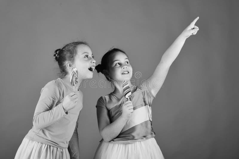 De meisjes eten grote kleurrijke zoete karamels Kinderen met nieuwsgierige gezichten stock foto