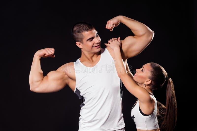 De meisjes hangt op bodybuilder ` s bicep royalty-vrije stock afbeelding