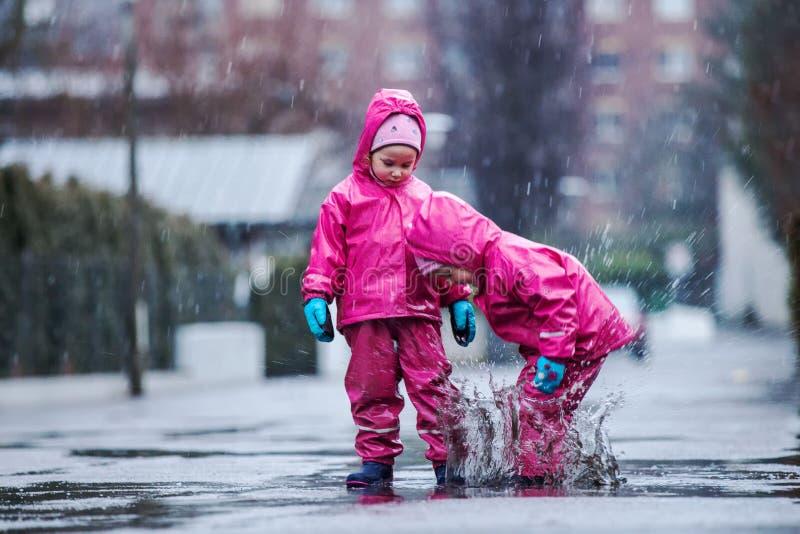 De meisjes hebben pret in water op straat in koude de herfstdag, meisjes die water in regen bespatten, vrolijke meisjes die van k stock foto