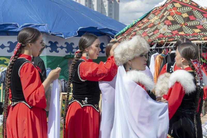 De meisjes kleden het andere meisje in het Bashkir nationale kostuum bij de Sabantuy-viering Front View royalty-vrije stock foto