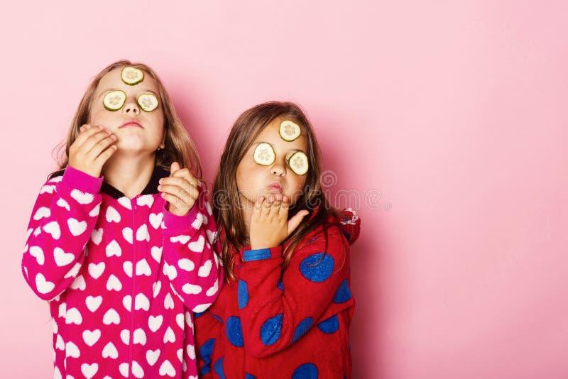 De meisjes in kleurrijke polka gestippelde pyjama's verzenden kussen royalty-vrije stock afbeelding