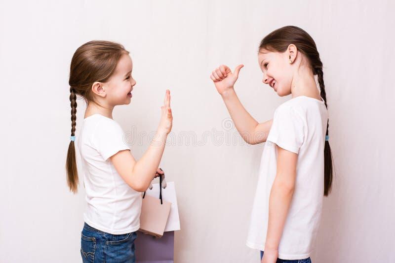 De meisjes komen na het winkelen samen en keuren het winkelen goed stock afbeelding