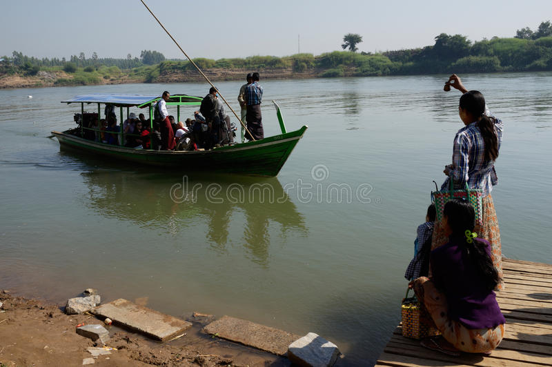 De meisjes in Myanmar ontmoeten boot met toeristen op de kust stock foto