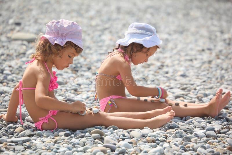 de meisjes speelt met kiezelsteenstenen. royalty-vrije stock afbeelding