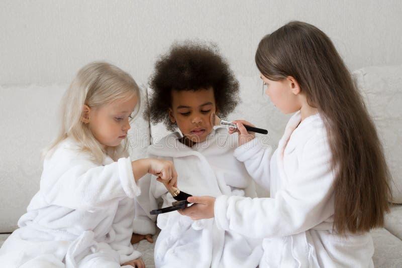 De meisjes spelen met make-up terwijl het zitten op de laag royalty-vrije stock foto