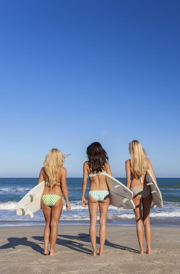 De Meisjes van de vrouwensurfer in Bikinis met Surfplanken bij Strand stock afbeelding