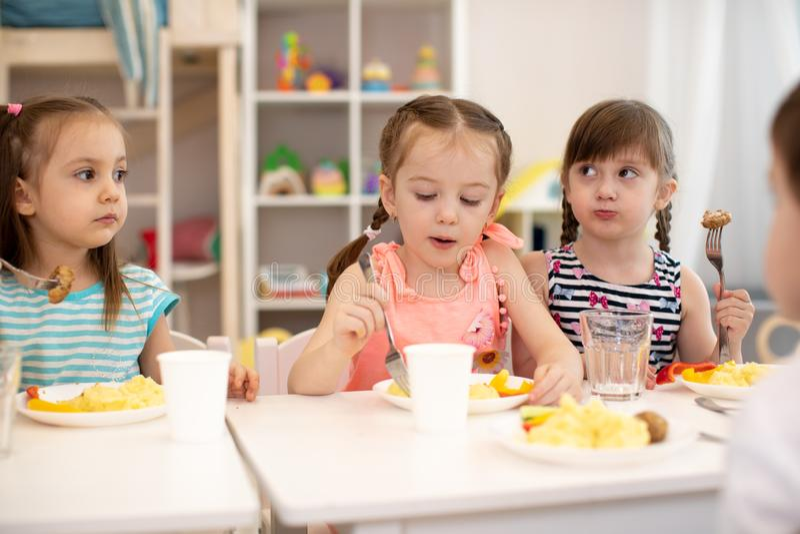 De meisjes van de groep kinderen die bij de lijst met lunch zitten en eten smakelijk royalty-vrije stock afbeeldingen