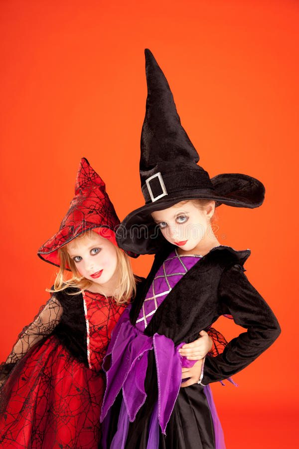 De meisjes van het de zusterjonge geitje van Halloween op sinaasappel royalty-vrije stock afbeelding