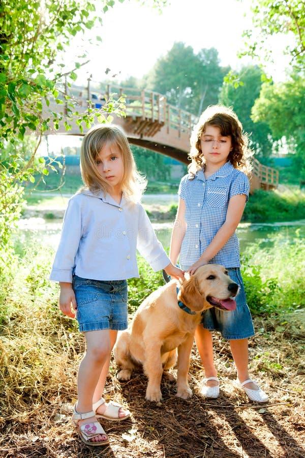 De meisjes van het jonge geitje met Gouden retrieverpuppy openlucht stock afbeelding