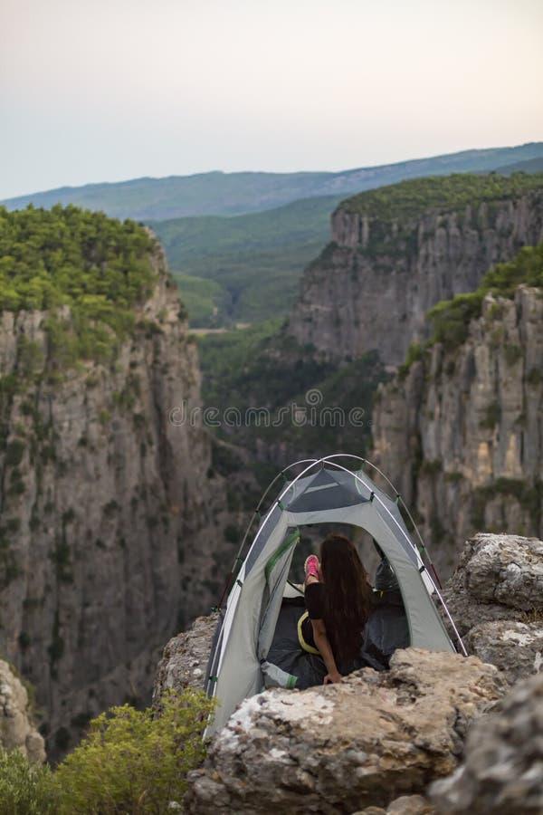 De meisjes van het jonge meisje dat een beeld van het landschap van binnenuit de kamptent nam royalty-vrije stock foto's