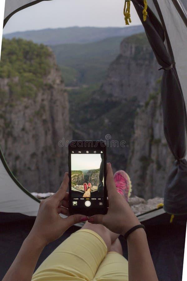 De meisjes van het jonge meisje dat een beeld van het landschap van binnenuit de kamptent nam royalty-vrije stock afbeelding