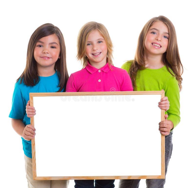 De meisjes van kinderen groeperen het exemplaarruimte van de holdings lege witte raad royalty-vrije stock foto's