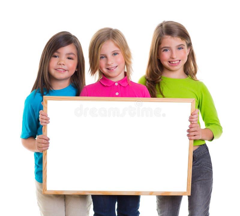 De meisjes van kinderen groeperen het exemplaarruimte van de holdings lege witte raad royalty-vrije stock afbeelding