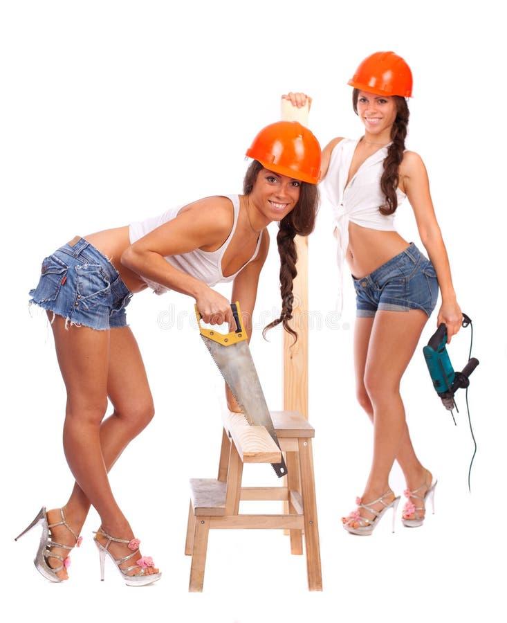 De meisjes van Tweeling in oranje helmen met een zaag stock foto