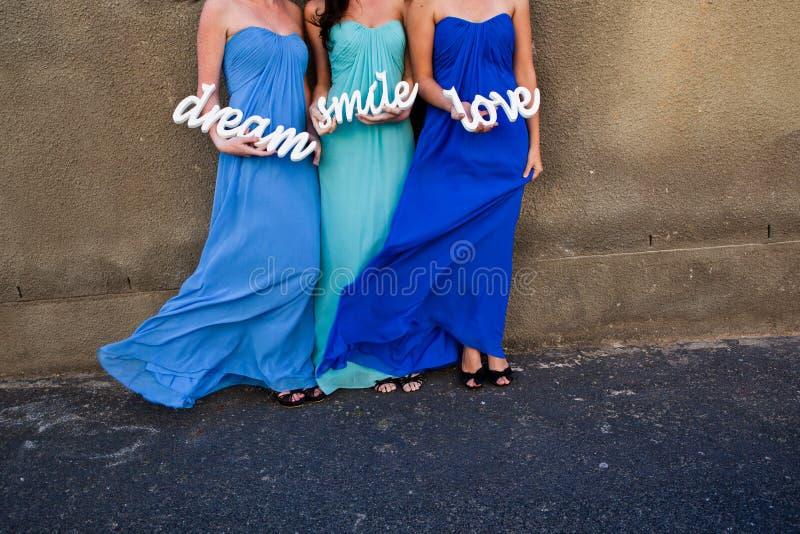 De meisjes van de vrouwenbruid in kleurrijke blauwe kleding steunen een teken Glimlach, liefde en droom royalty-vrije stock fotografie