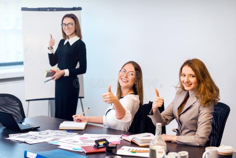 De meisjes werken in het bureau en tonen aan dat allen goed is stock foto