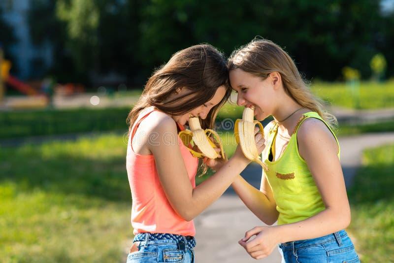 De meisjes zijn schoolmeisjes Eet bananen voor een onderbreking De zomer in aard Het concept een gezonde ontbijtmaaltijd De emoti royalty-vrije stock afbeeldingen
