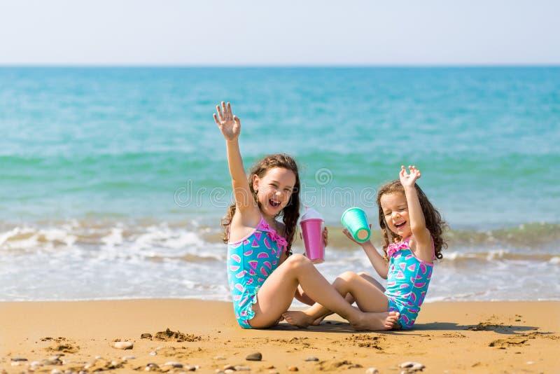 De meisjes zitten zitten tegenover elkaar, drinken van gekleurde mooie cocktailglazen en hebben pret De vakantie van de familie royalty-vrije stock foto's