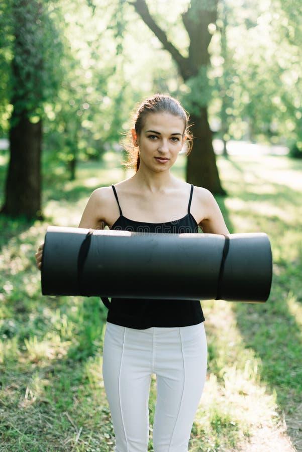 De meisjesatleet met een karemat in haar handen loopt in het park stock fotografie