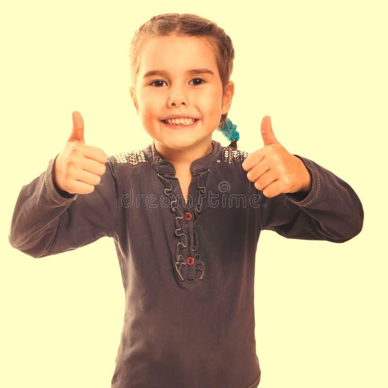 De meisjesbaby hief haar duimen omhoog geïsoleerd het glimlachen symbool op wijst op stock fotografie