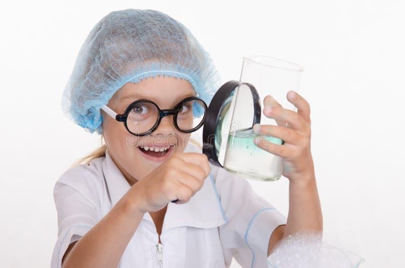 De meisjeschemicus onderzoekt fles onder een vergrootglas stock foto's