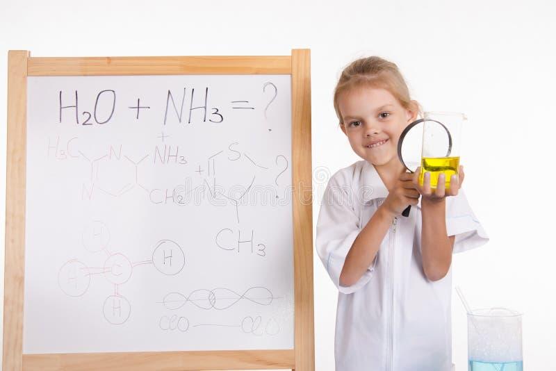 De meisjeschemicus onderzoekt vloeistof in fles onder een vergrootglas royalty-vrije stock afbeeldingen