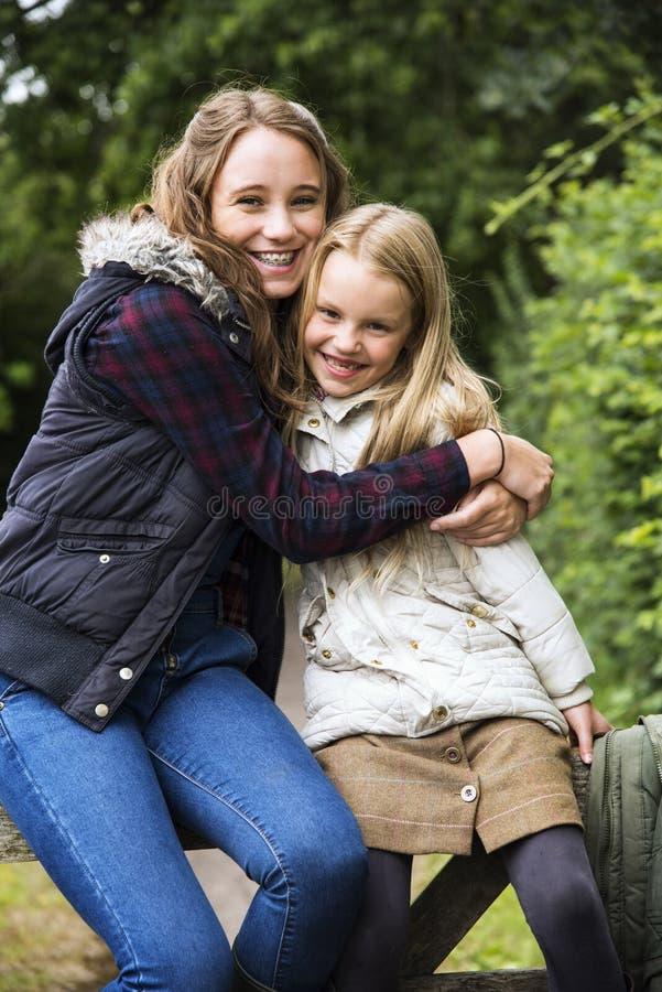 De Meisjesconcept van zusterhug togetherness outdoors stock afbeeldingen