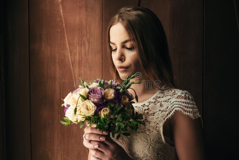 De meisjesholding bloeit in handen, jonge mooie bruid in wit het huwelijksboeket van de kledingsholding, boeket van bruid van roz royalty-vrije stock fotografie