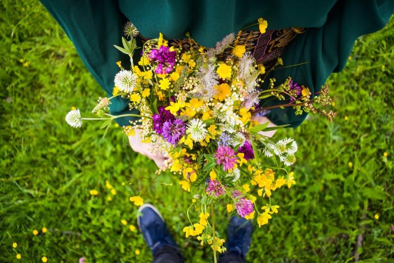 De meisjesholding in haar overhandigt een mooi boeket met multi-colored wilde bloemen Verbazende bos van wilfbloemen in de aard royalty-vrije stock afbeelding