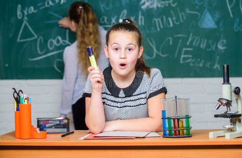 De meisjesklasgenoten bestuderen chemie De chemische reacties van microscoopreageerbuizen Leerlingen bij de les van de bordchemie royalty-vrije stock foto