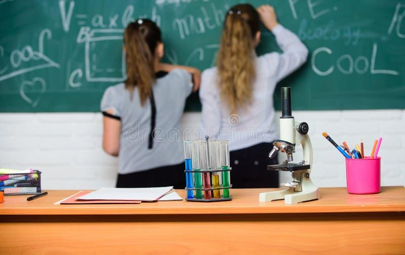 De meisjesklasgenoten bestuderen chemie Microscoop en reageerbuizen op lijst chemische reacties Maak het bestuderen van chemie royalty-vrije stock foto's