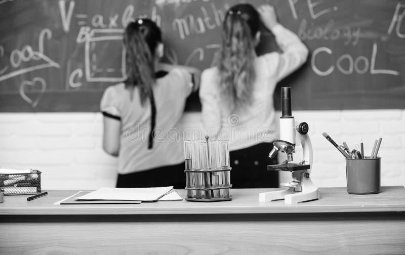 De meisjesklasgenoten bestuderen chemie Microscoop en reageerbuizen op lijst chemische reacties Maak het bestuderen van chemie royalty-vrije stock afbeelding