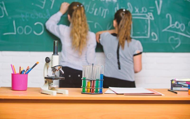 De meisjesklasgenoten bestuderen chemie Microscoop en reageerbuizen op lijst chemische reacties Maak het bestuderen van chemie royalty-vrije stock afbeeldingen