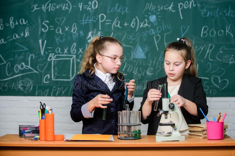 De meisjesklasgenoten bestuderen chemie Microscoop en reageerbuizen op lijst Voer chemische reacties uit Basiskennis van stock foto's
