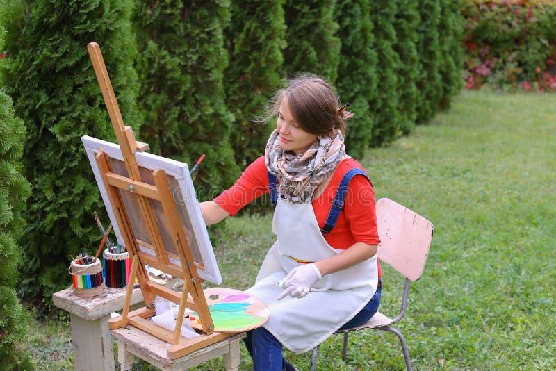 De meisjeskunstenaar schildert beeld en zit op stoel aan schildersezelkanten van t stock afbeelding