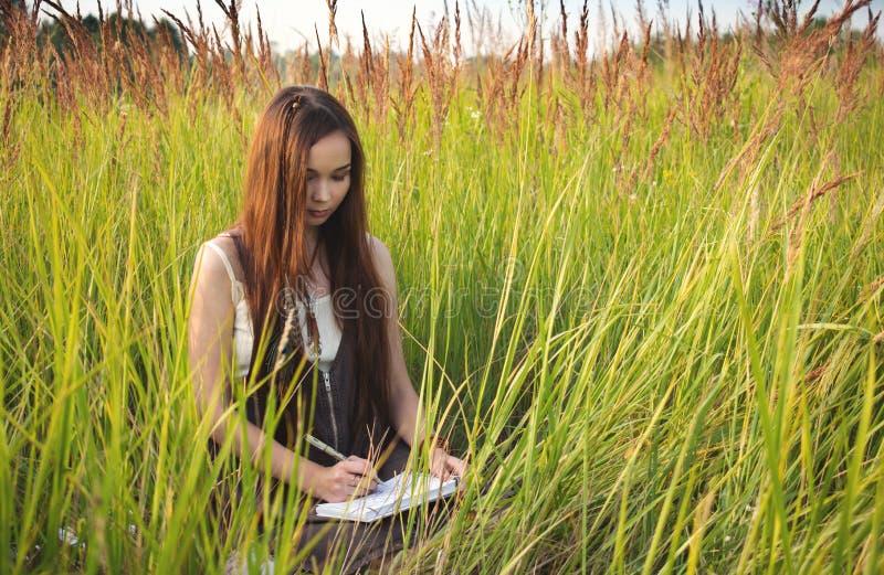 De meisjeskunstenaar trekt in een sketchbook in de zomer stock afbeelding