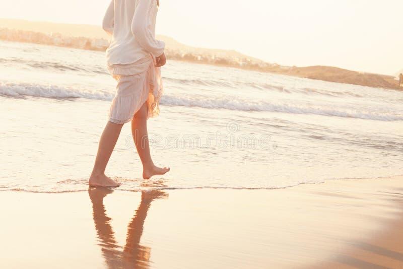De Meisjeslooppas blootvoets langs Sandy Beach van het Overzees stock afbeelding